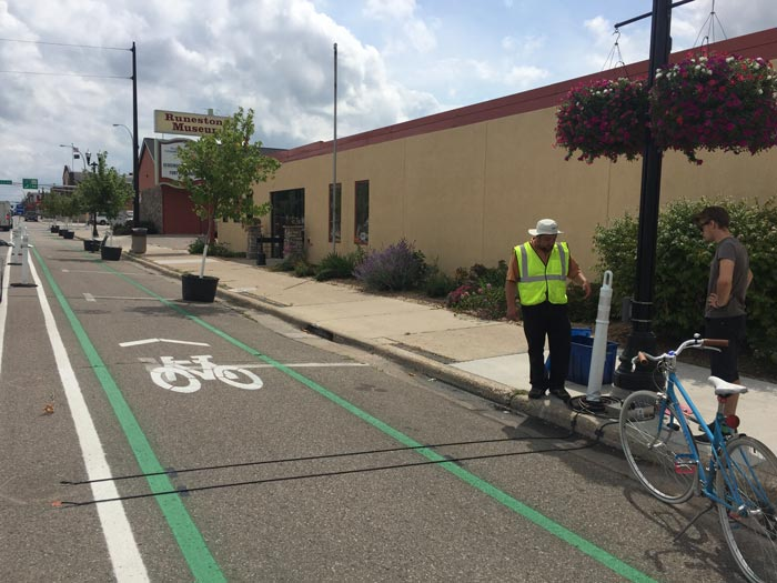 Two people installing bicycle and pedestrian counters along a road and sidewalk in Alexandria, Minnesota.